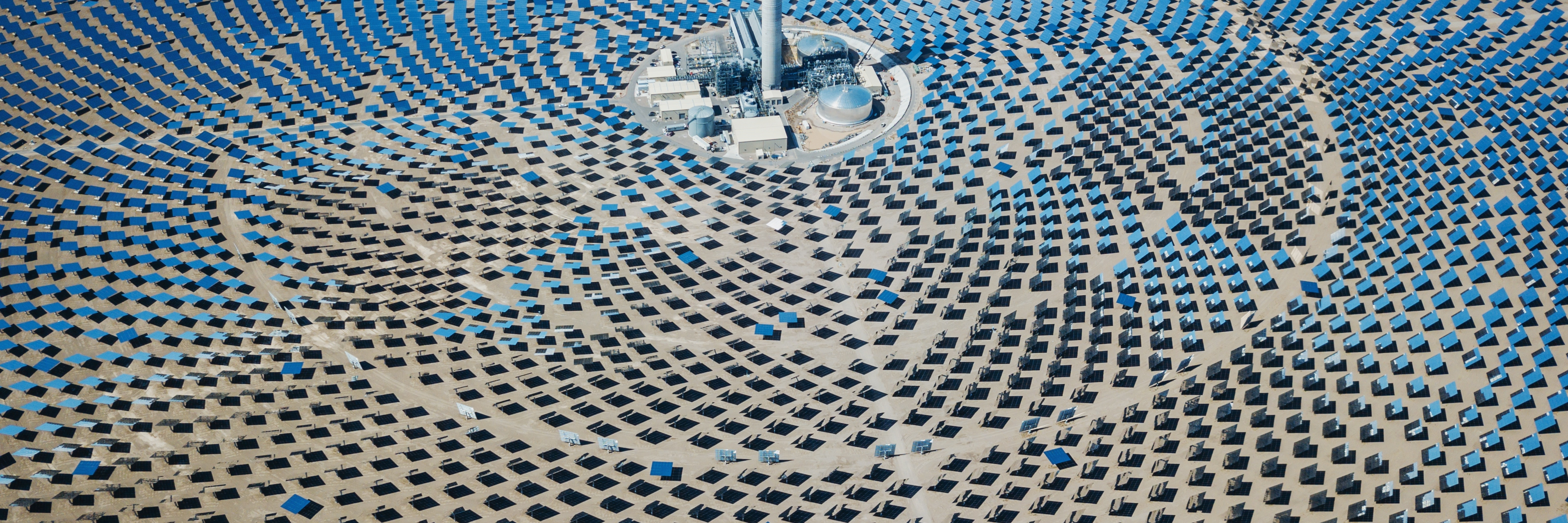 Aerial view of solar thermal power plant station in the desert to the horizon.