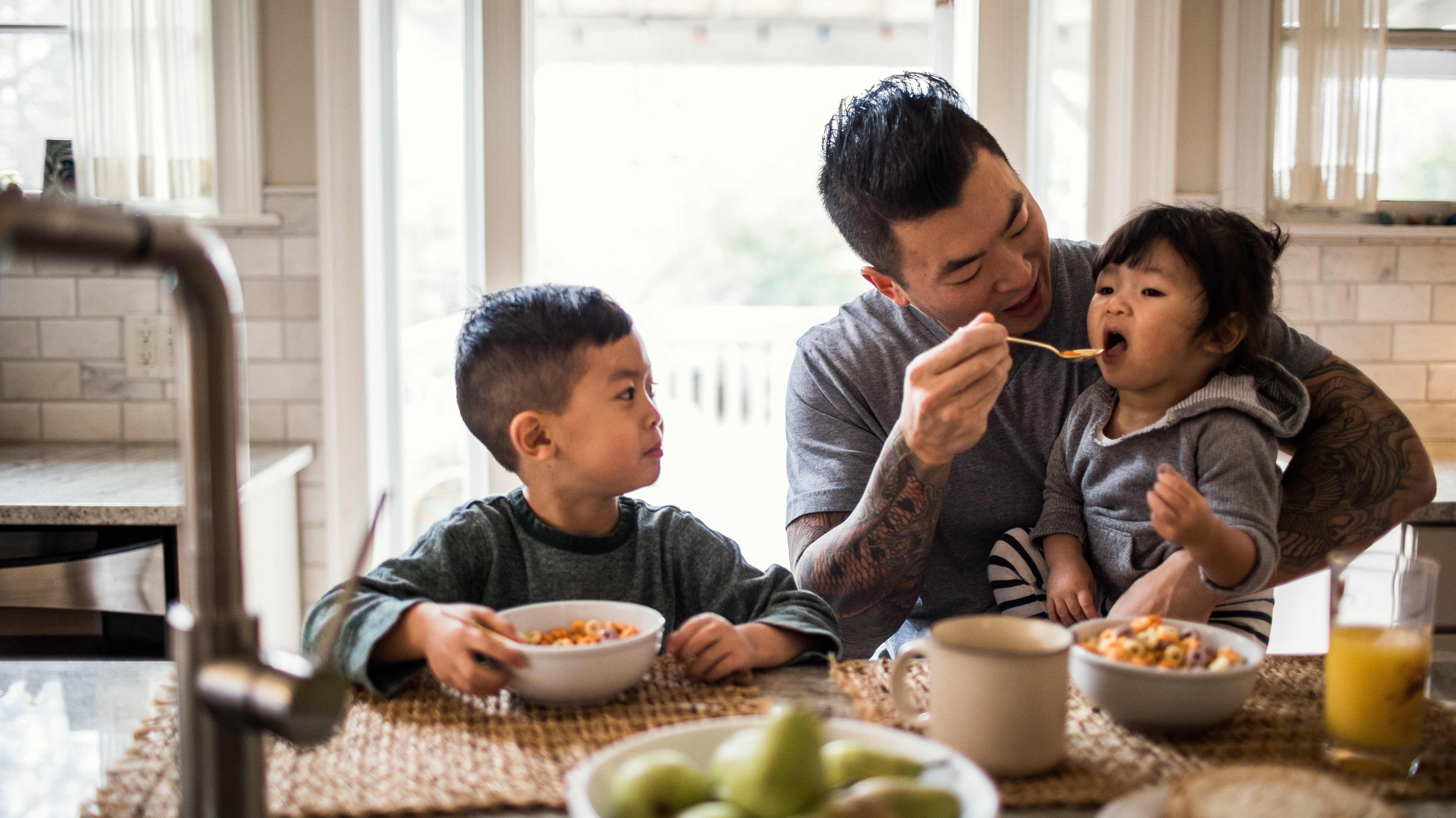 A father feeding his children at the table in their home.