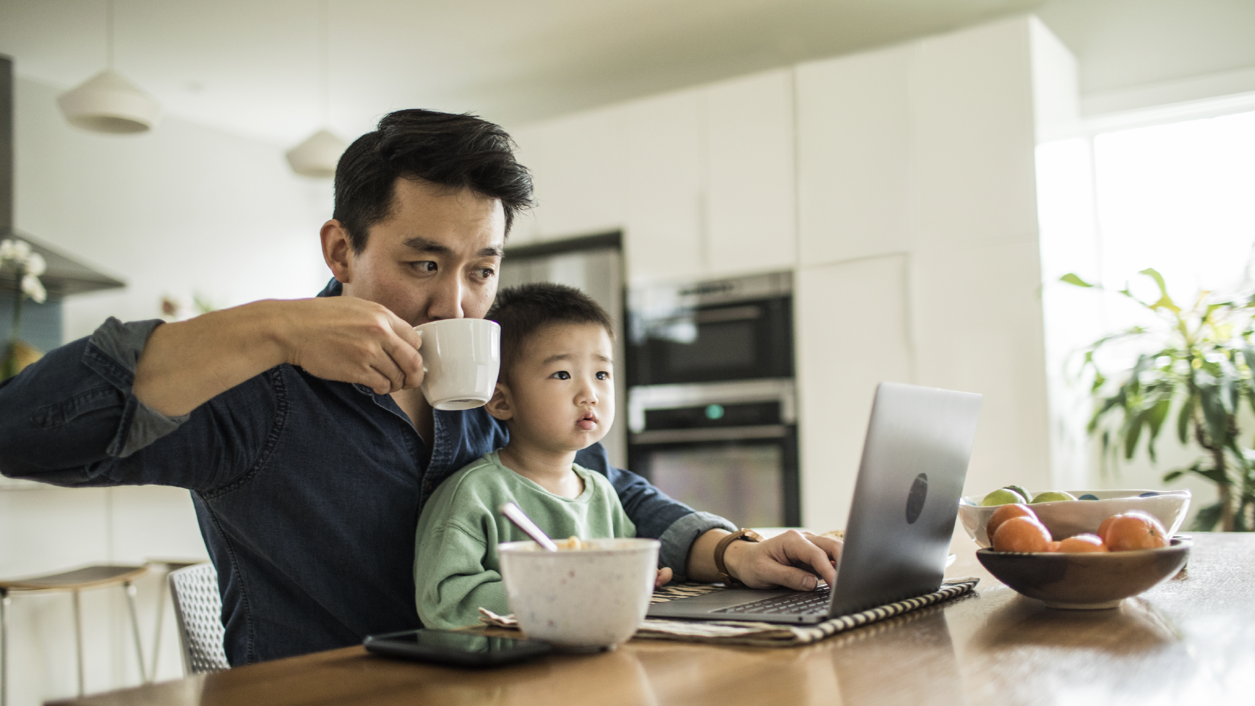 Father and son at kitchen table on laptop