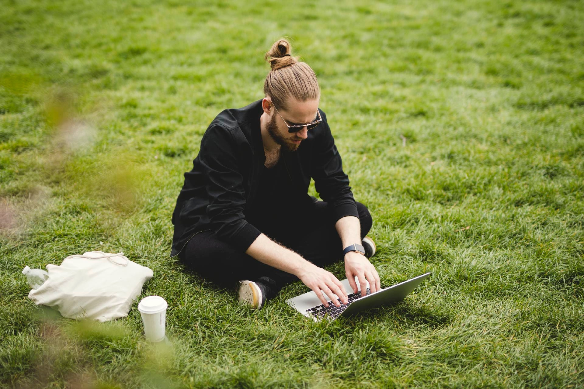 Man using a laptop in a park