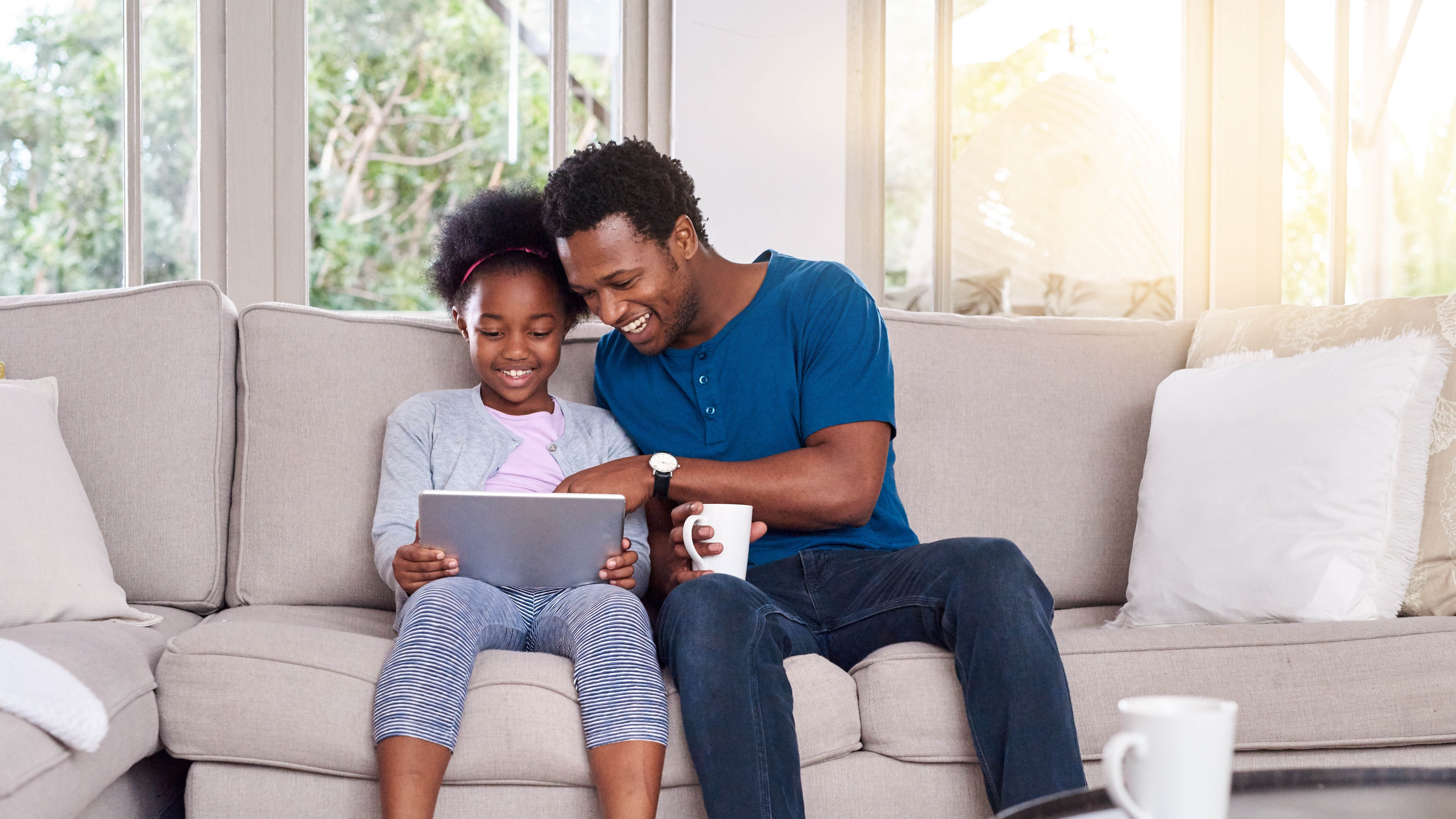 Smiling father and son using digital gadgets in living room