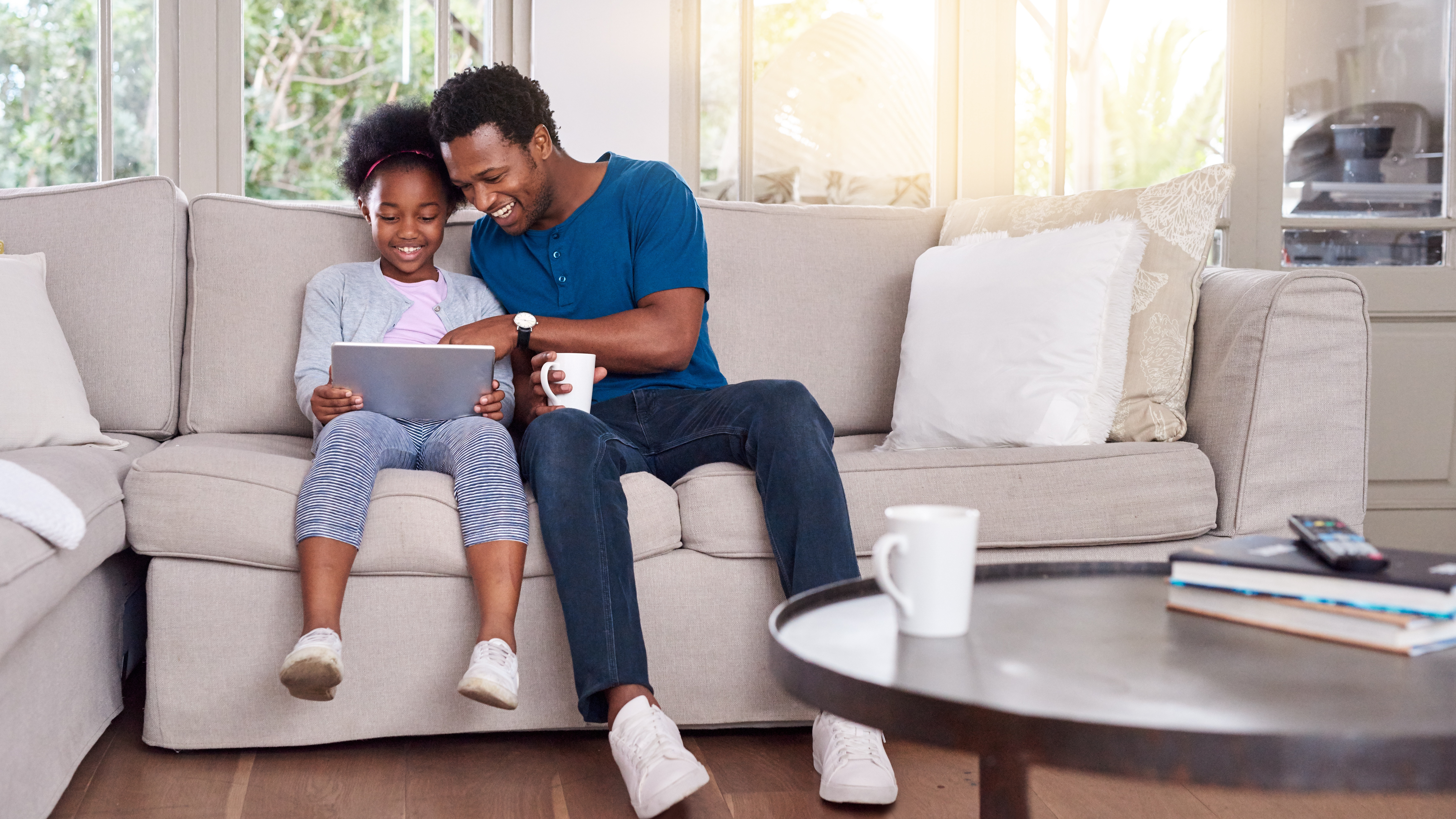 Shot of a father and his little daughter using a digital tablet together at home