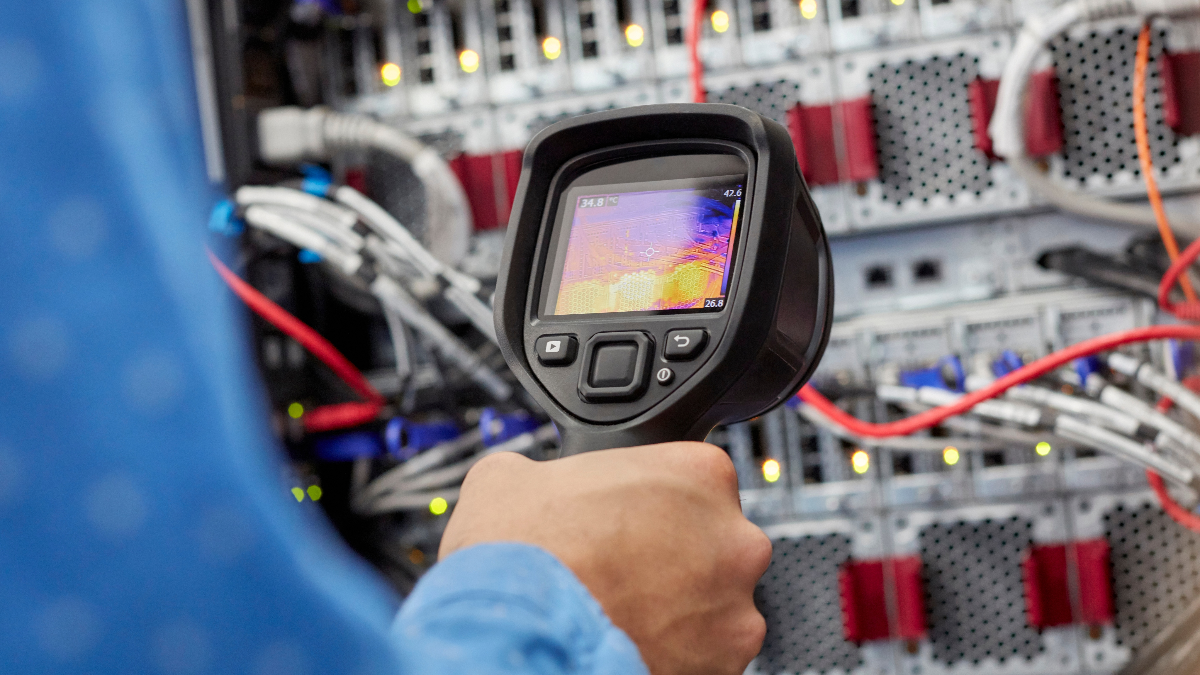 IT technician using diagnostic thermal imagining camera equipment in server room